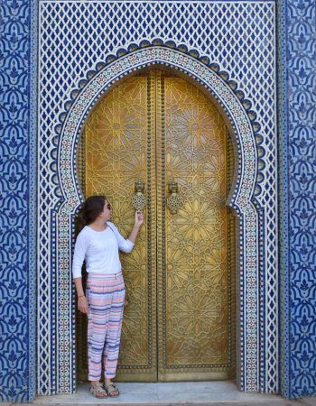 Sarah Proper standing in front of a gold door encased in a Moroccan blue tile