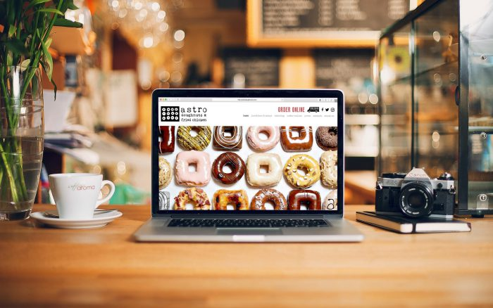 Astro Doughnuts homepage is featured on a laptop in a coffee shop like environment
