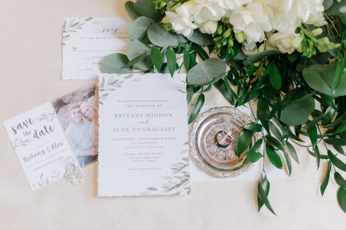 Save the Dates amongst the invitation suite, rings, and eucalyptus